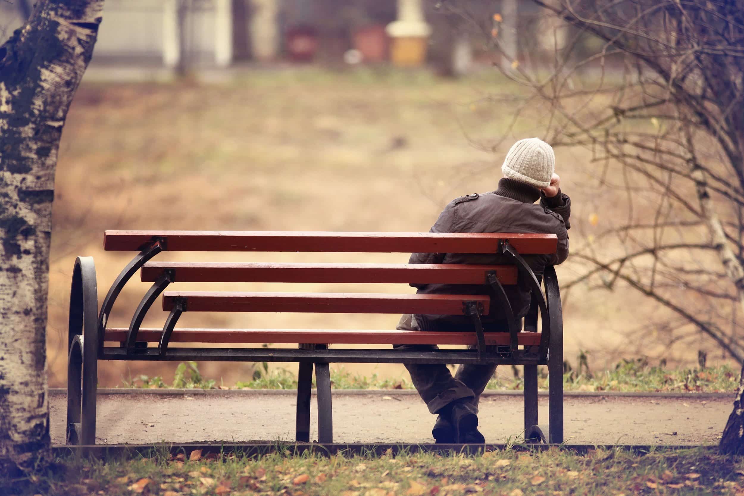 mid thirties single man lonely sitting on bench coping