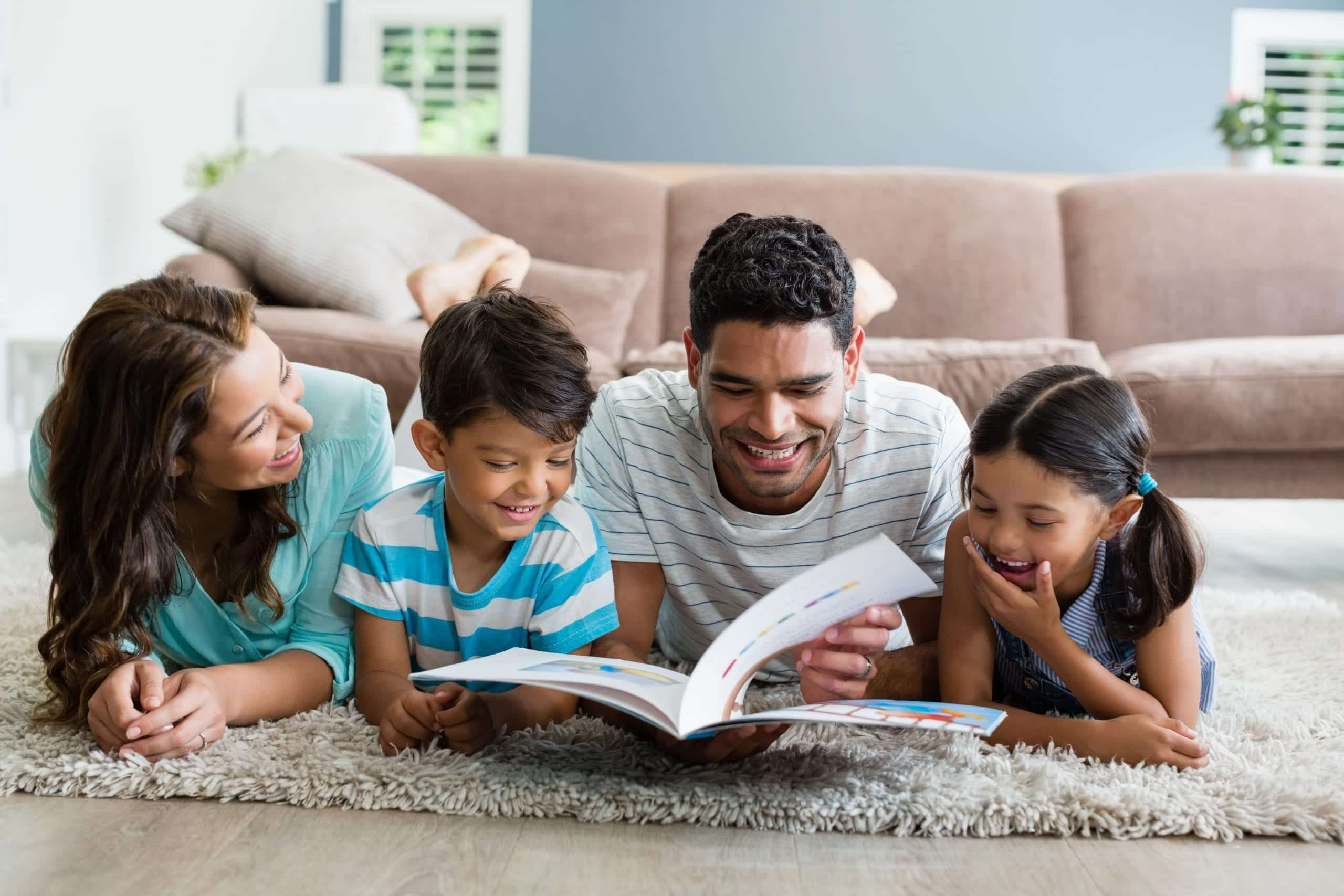 preparing kids to go back to school parents and children lying down reading book
