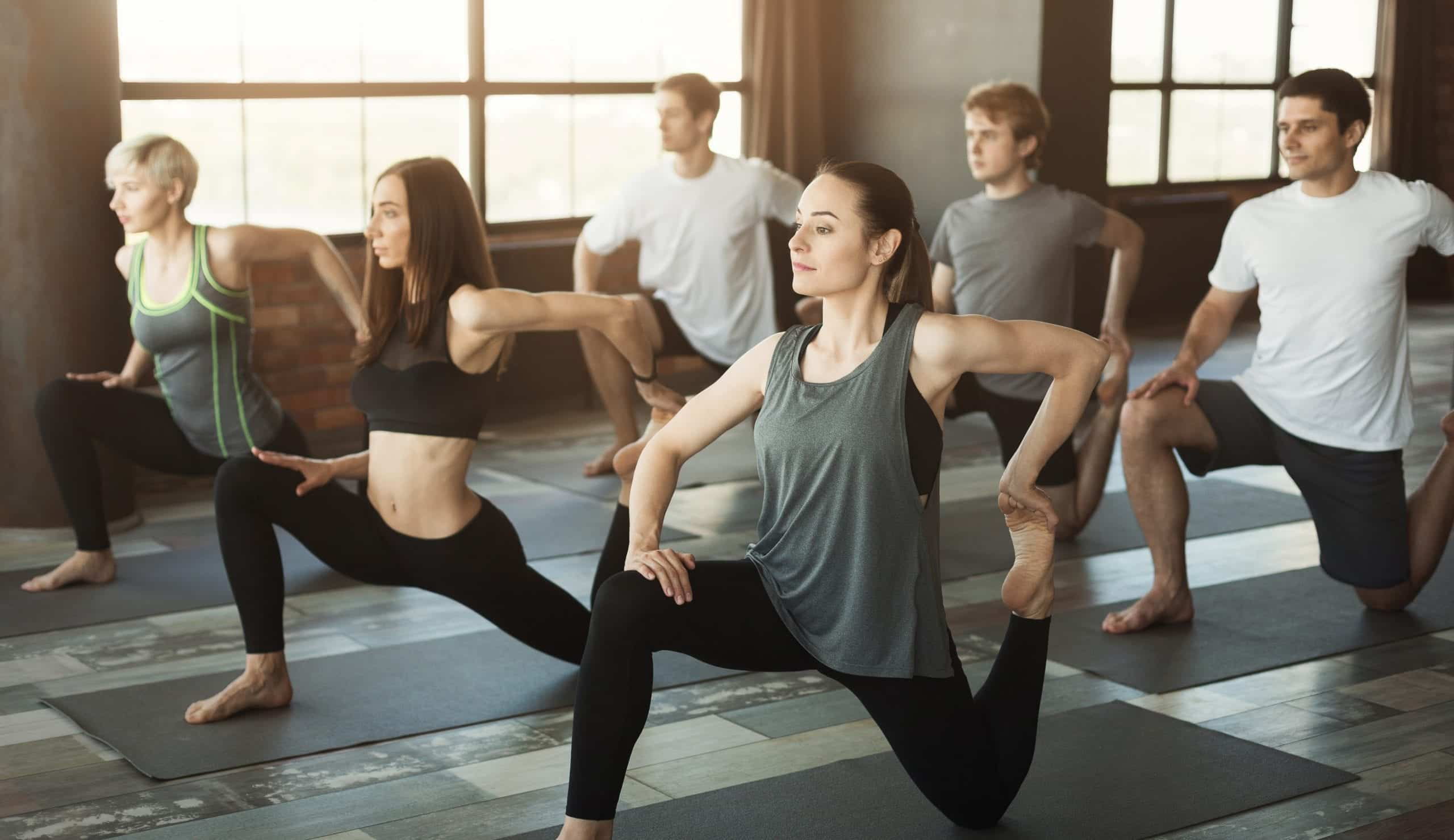 benefits of pilates Fitness or yoga practice. Group of fit people working out in sports club, doing warming up exercises, stretching feet, copy space