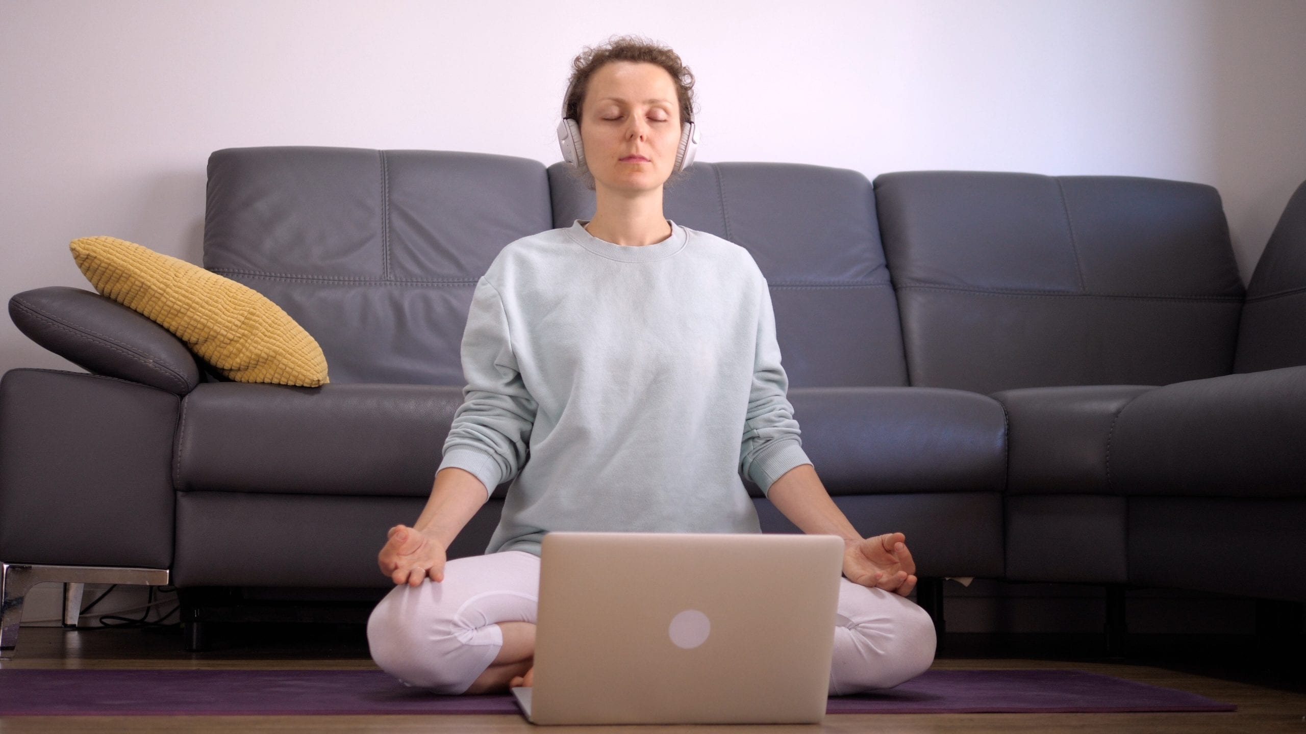 mindfulness guided meditation practicing by woman sitting on floor with headphones and laptop