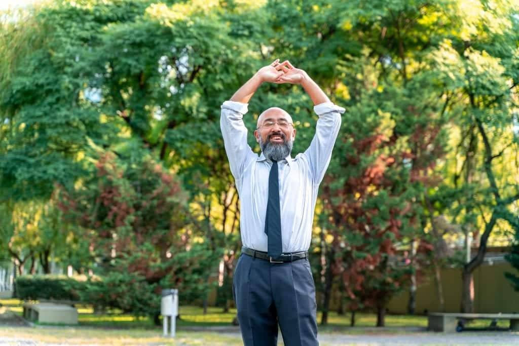 Asian businessman stretching in a park in an urban environment.