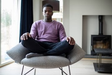 Boy meditating on chair to stop thinking about something