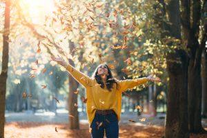 Casual joyful woman having fun throwing leaves in autumn at city park.