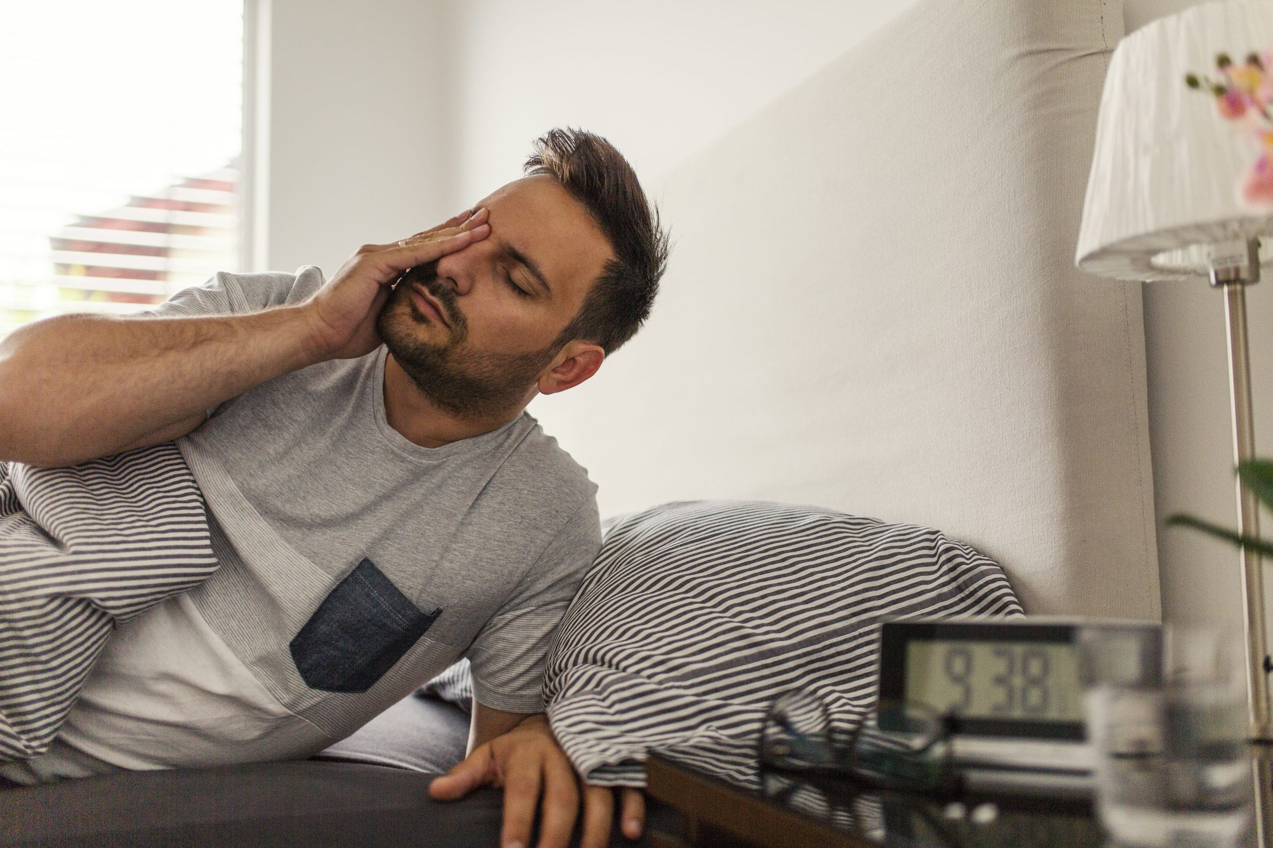 Man tired waking up in the morning and wiping eyes with his fingers