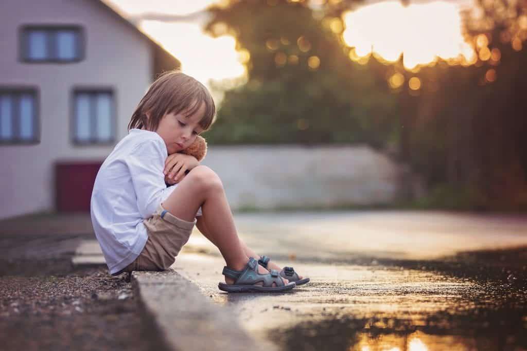 Sad little boy, sitting on the street in the rain, hugging his teddy bear, summertime on sunset