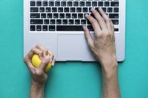 Office worker typing email on computer, feels stressed and nervous, holds a stress ball in her hand