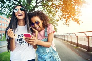 Giddy female friends falling over one another as they listen to their mobile music device