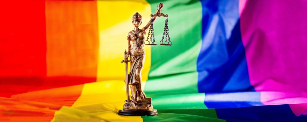Statue of justice symbol of law and justice with lgbt flag in rainbow colours. Lgbt rights and law
