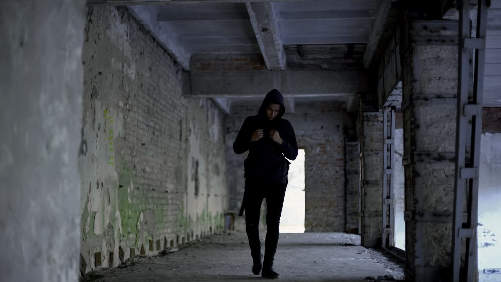 Lonely boy walking in abandoned building, afro-american has no friends, racism