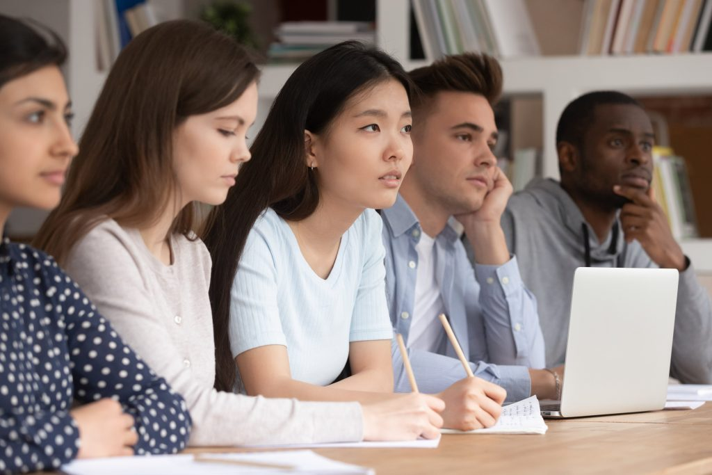 Attentive multicultural diverse young people sit at desk listen to teacher talk giving lecture or explaining material, concentrated multiethnic students make noted write down during lesson at college