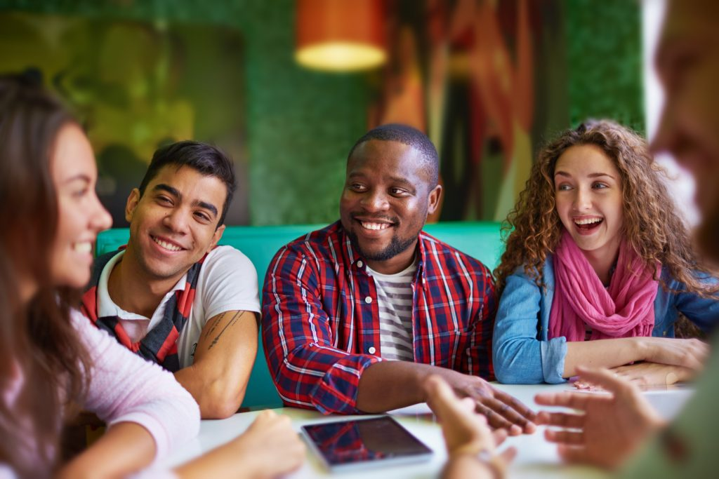 Happy teenagers sitting in cafe and discussing news