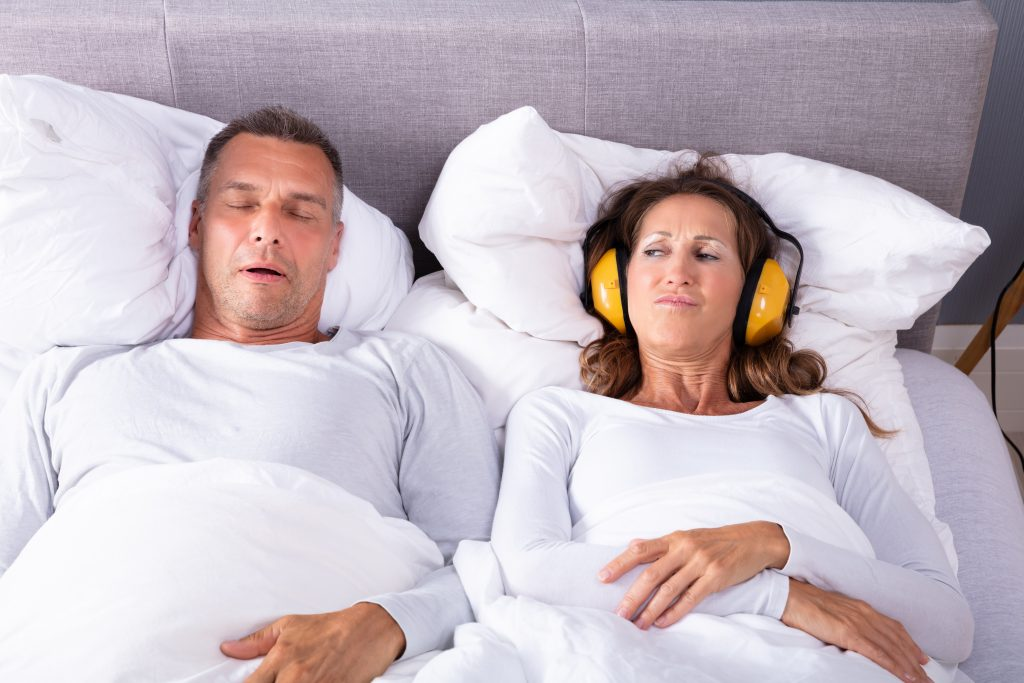 Mature Woman Covering Her Ears With Headphone While Man Snoring In Bed