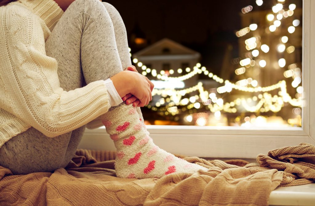 childhood, sadness and people concept - close up of girl in sweater sitting on sill at home window over christmas lights background