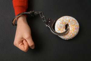 Woman handcuffed to tasty doughnut on dark background. Concept of addiction