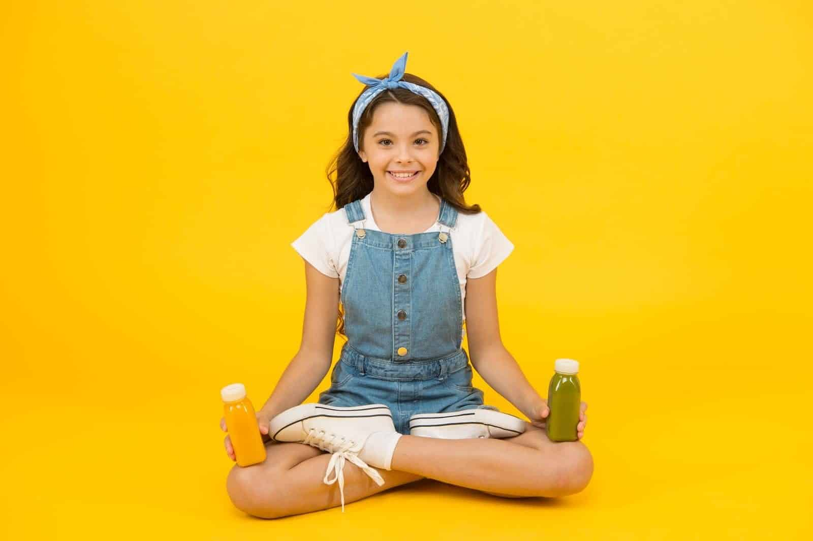 Yoga training. KId girl sit meditate. Meditating practice. Good vibes. Peaceful meditating. Vegetarian smoothie drink. Learn meditating techniques. Stay positive and optimistic. Healthy way of life.