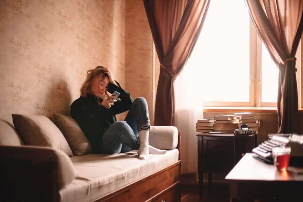 Woman on couch looking at phone stressed