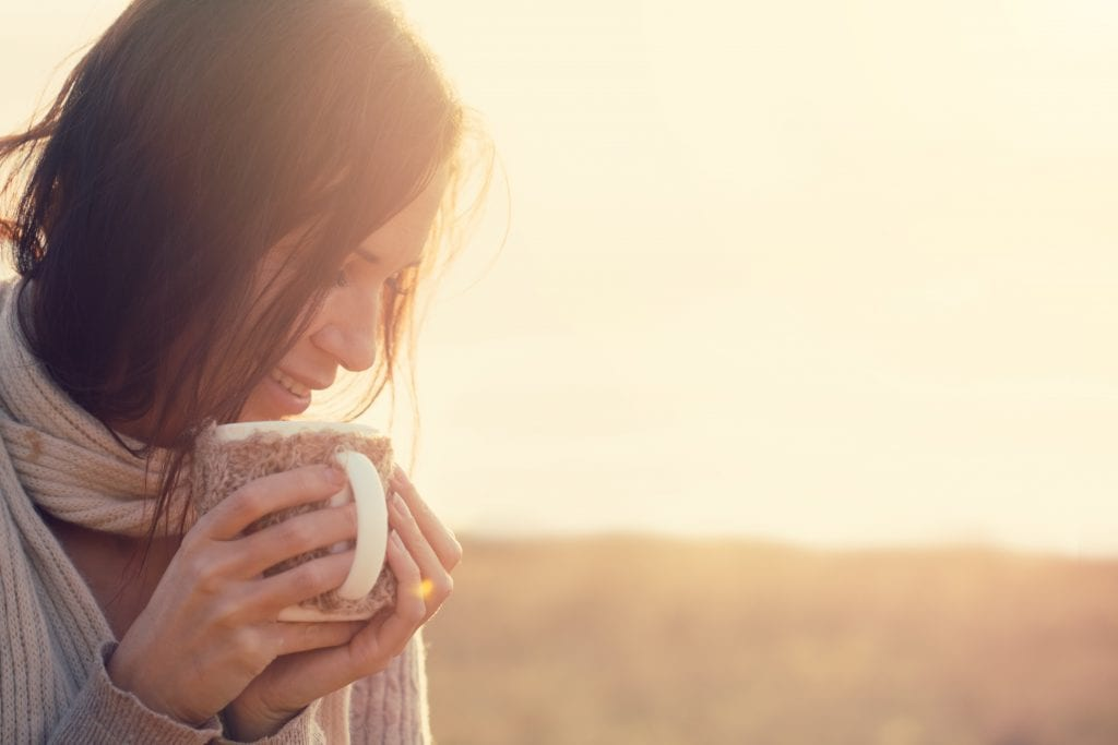 Woman holding mug self soothing anxieties away
