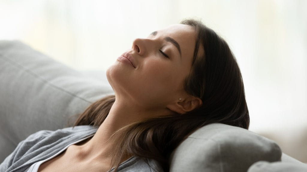 young woman deep breathing at home for health benefits
