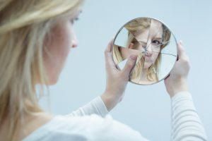 girl with low self esteem low self worth looking in broken mirror