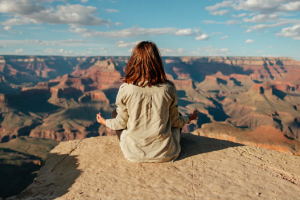 woman sitting on the peak of a mounting meditating taking deep breaths