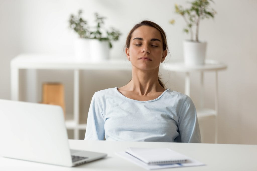 calm woman deep breathing meditating at work