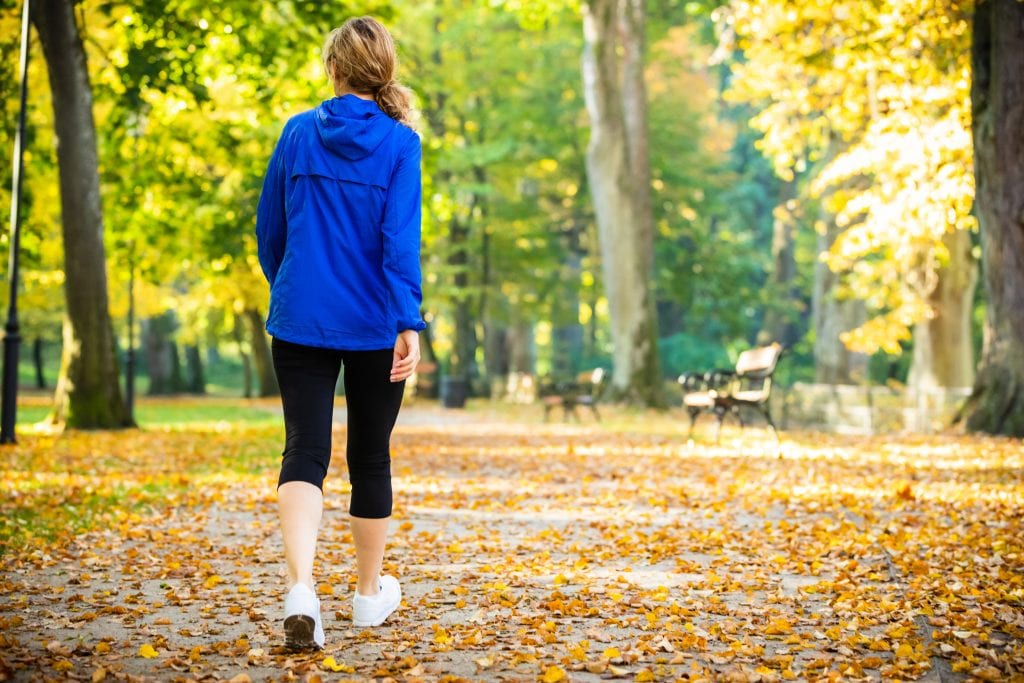 woman walking in park light exercise to calm panic attack in fall