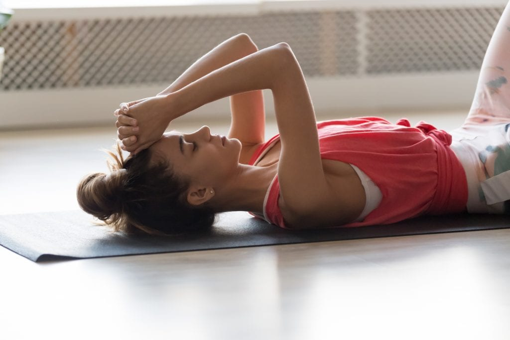 woman deep breathing after intense workout lying on mat