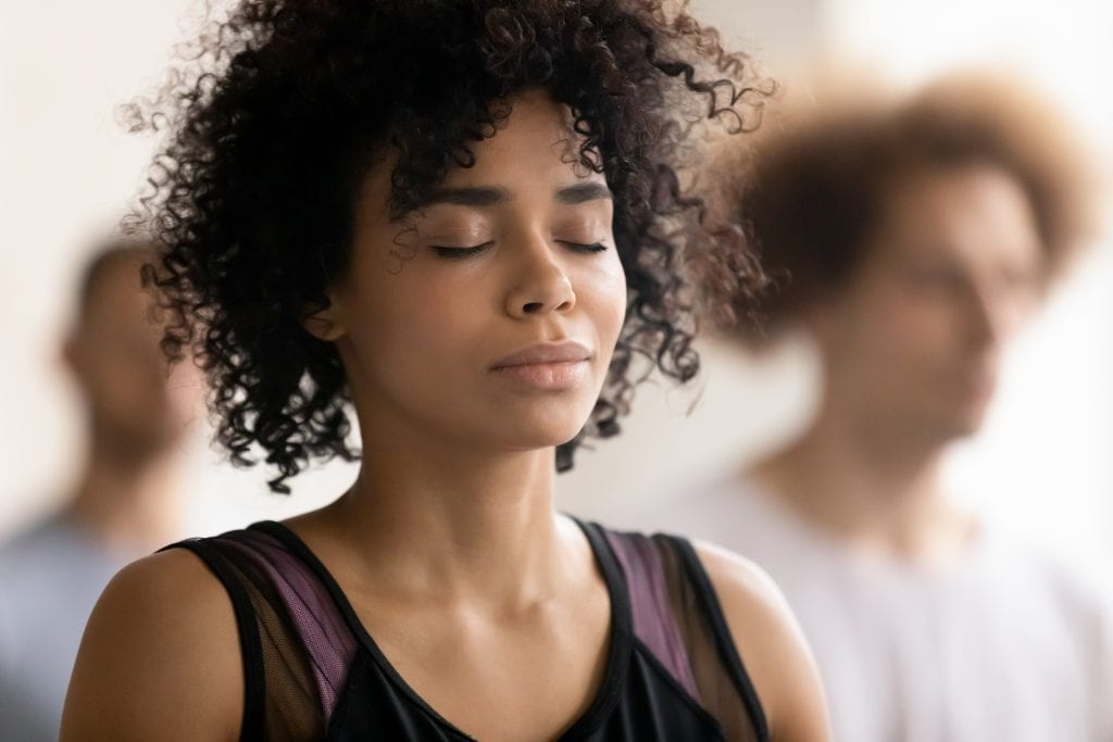 young peaceful woman enjoying deep breathing mindfulness meditation.
