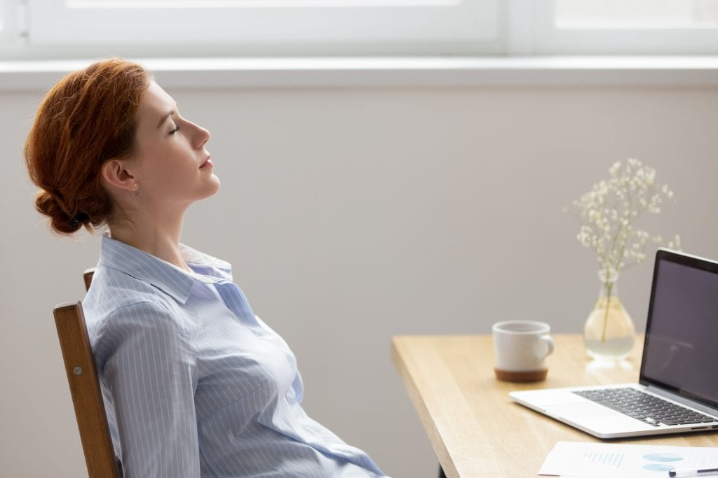 Side view female resting with closed eyes at work staying present to deal with social anxiety