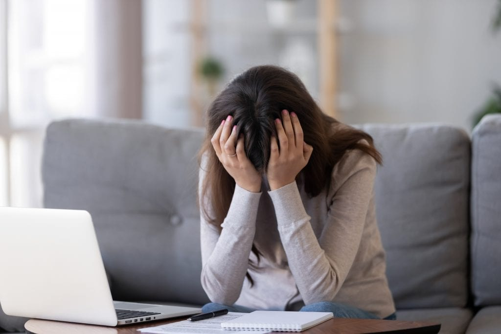 upset woman with head in hands experiencing social anxiety during work meeting