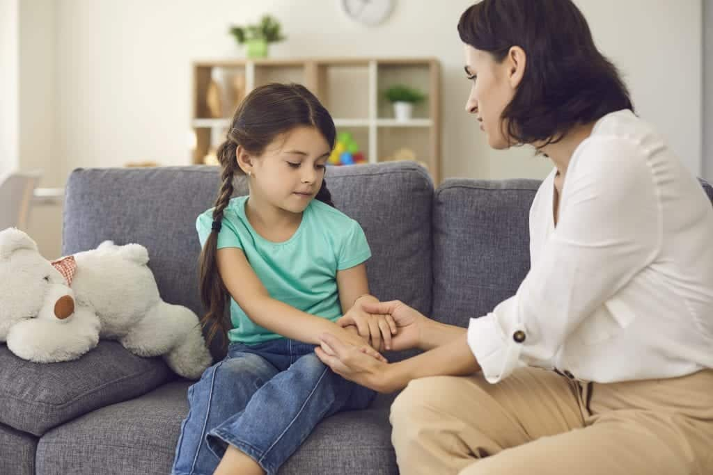 caregiver sitting with daughter, holding her hands, talking to her dealing with bullying