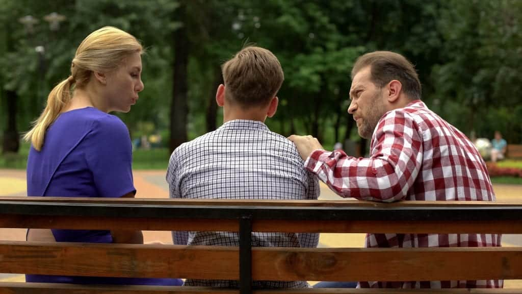 caregivers dealing with bullying talking to son on park bench