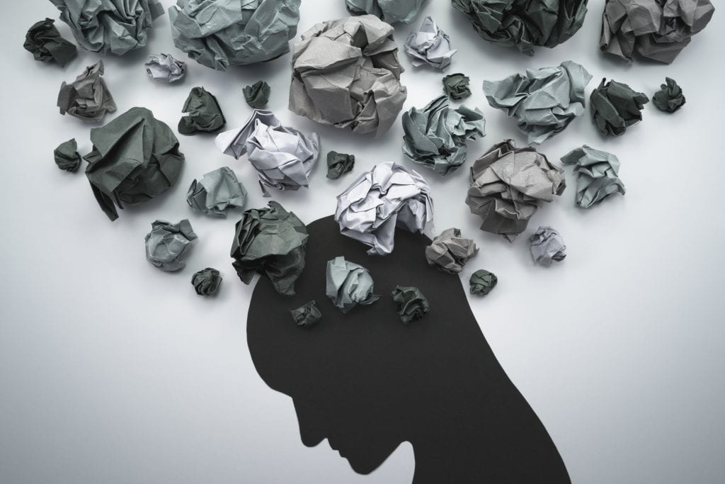 feelings of anxiety. Silhouette of troubled person head. Concept image of anxiety and negative emotion. Waste paper and head silhouette.
