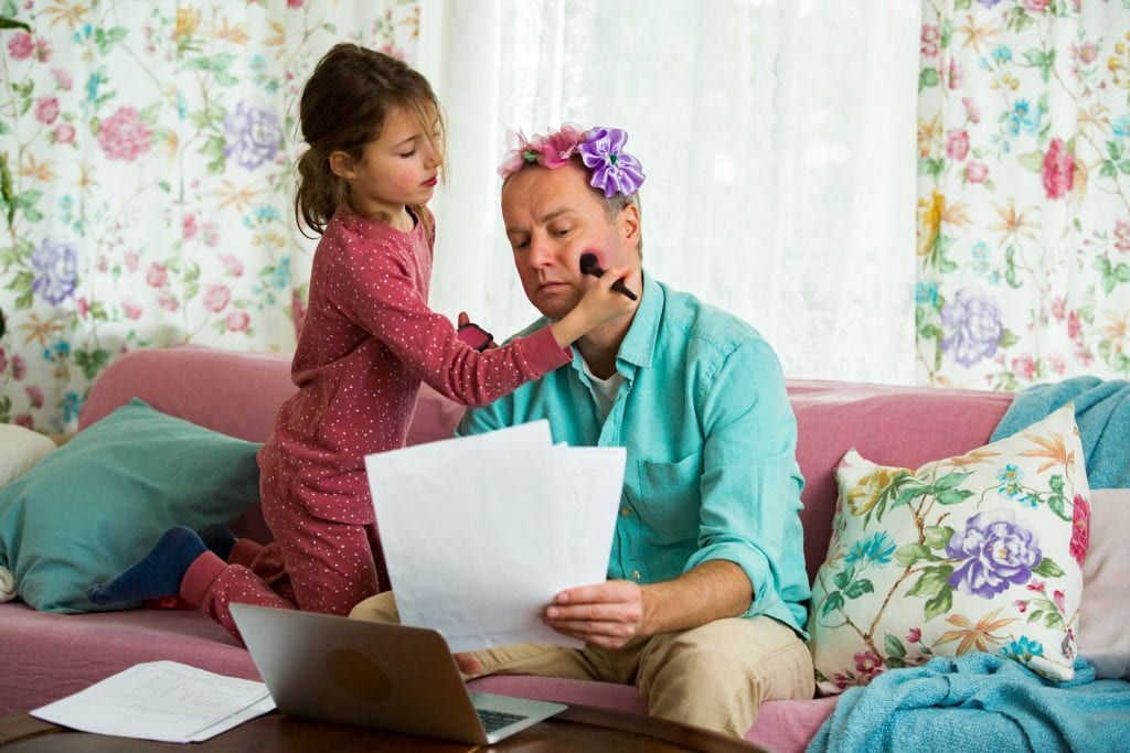 Child playing and disturbing father working remotely from home