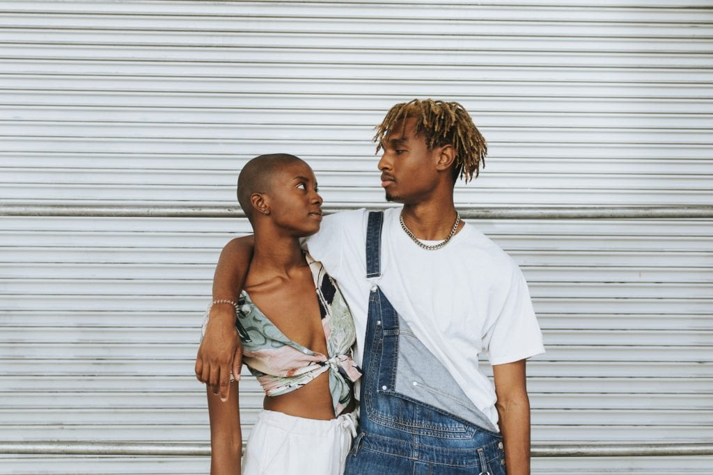 African american couple posing by a wall